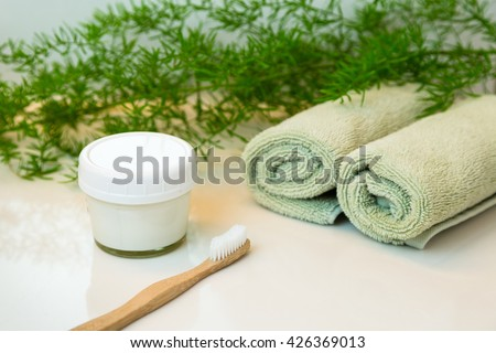 Homemade toothpaste in mason jar and bamboo bio-degradable, compostable toothbrush. Rolled green towels in a spa setting. Green plant decor in background. Bathroom white countertop. - stock photo