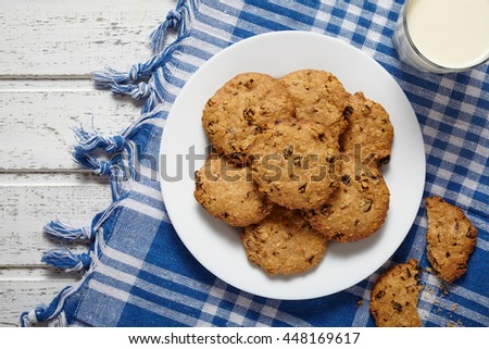 Homemade traditional oatmeal cookies with raisins and chocolate healthy sweet dessert snack food with glass of milk and blue napkin on white vintage wooden table background. - stock photo