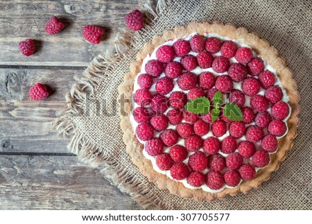 Homemade traditional sweet raspberry tart pie with cream and mint on vintage wooden table background. Rustic style and natural light. - stock photo