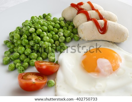 Homemade turkey sausages in ketchup and a garnish of green peas and mini tomatoes - stock photo