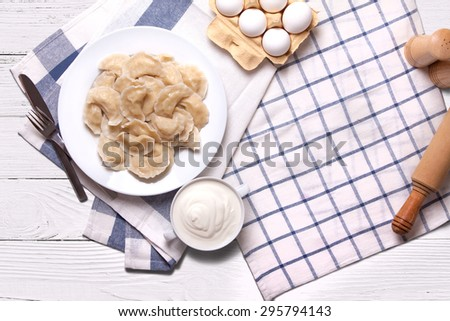 Homemade varenyky Ukrainian traditional dish. Top view. Perogy, stuffed dumplings served on white plate. Ukrainian cuisine. Background with food and decorations. - stock photo