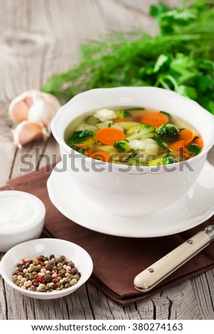 Homemade vegetable soup with broccoli, green peas, carrots and celery in a white bowl on a wooden background in rustic style, selective focus - stock photo