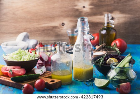 Homemade vinaigrette and ingredients.  Organic vegetables on rustic table. Salad ingredients. Vegetarian food, concept, rustic style - stock photo