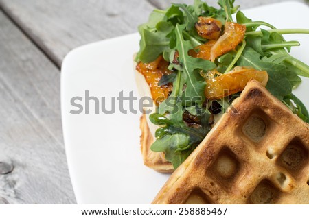 Homemade waffle burger on a white ceramic plate against wooden background - stock photo