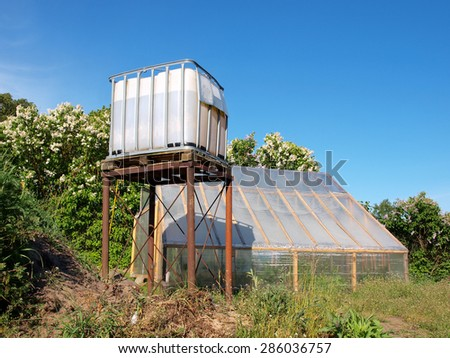 Homemade water tower from plastic container on metal stands for greenhouse watering      - stock photo