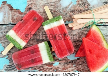Homemade watermelon ice pops with melon slices against rustic wood background - stock photo