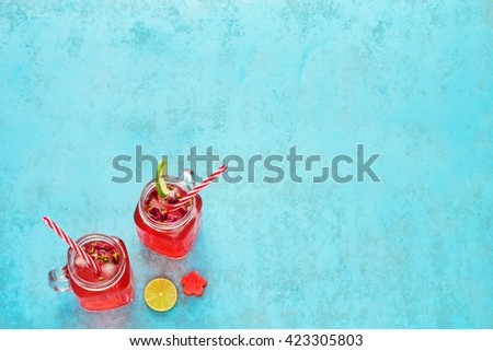 Homemade watermelon lemonade / watermelon cocktail in mason jar with red striped straw on a blue background - stock photo