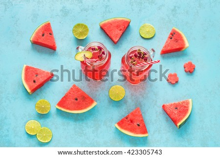 Homemade watermelon lemonade / watermelon cocktail with lime in mason jars with red striped straw. Blue background.  - stock photo
