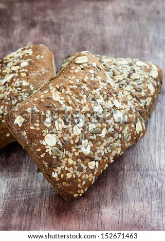 Homemade whole grain bread over wooden background, selective focus, closeup - stock photo