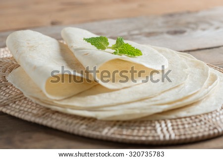 Homemade whole wheat flour tortillas on wooden table. - stock photo