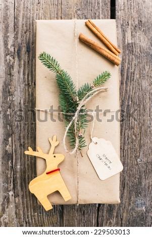 Homemade wrapped christmas present on wooden surface - stock photo