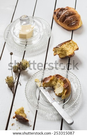 Homemade Yeasted Honey Cornbread with Butter on a Crystal Plate and Dried Flowers - stock photo