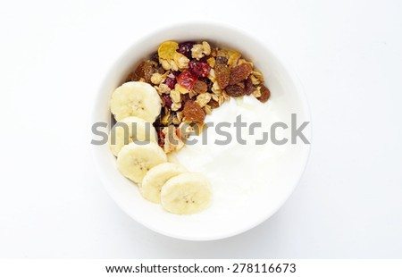 homemade yoghurt with muesli and banana in white bowl on white wooden table.  - stock photo