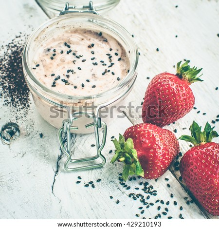 Homemade yogurt in a jar with strawberry, seeds and cacao. Dessert with strawberries on a white wooden background. Fresh juicy strawberry with yogurt. Selective focus. Shallow depth of field. Square. - stock photo