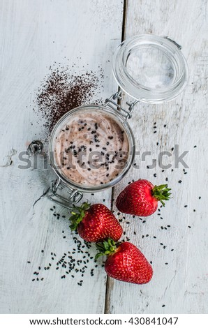 Homemade yogurt in a jar with strawberry, seeds and cacao. Dessert with strawberries on a white wooden background. Fresh juicy strawberry with yogurt. Directly above. Top view. Vertical. - stock photo