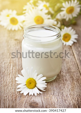 homemade yogurt in  glass jar ,  bouquet camomiles on old wooden background (selective focus) - stock photo