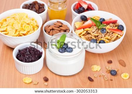 homemade yogurt with fresh berries and breakfast foods on table, horizontal - stock photo
