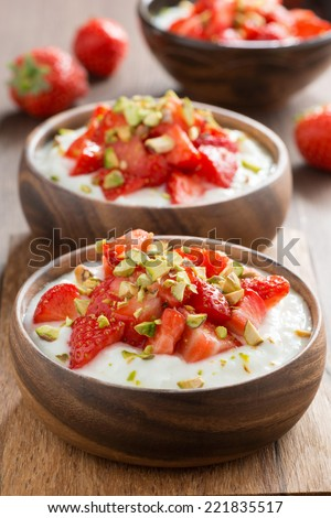 homemade yogurt with fresh strawberries and pistachios, close-up, vertical - stock photo