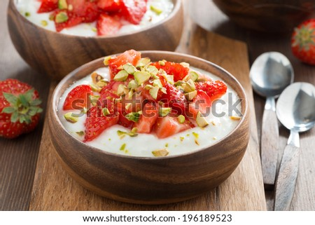 homemade yogurt with fresh strawberries and pistachios in a wooden bowl, close-up - stock photo