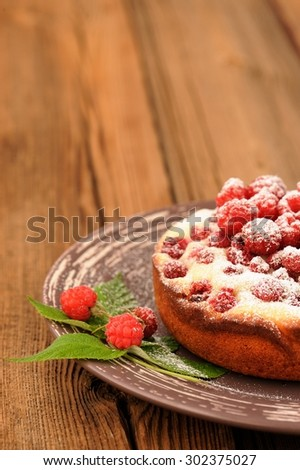 Homemade yummy cake with fresh wild raspberries and leaves decorated with icing sugar in brown plate on old rustic table copyspace - stock photo
