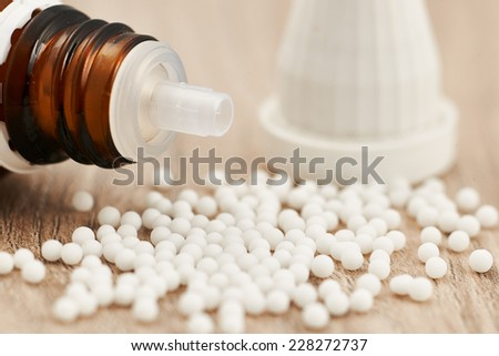 Homeopathic granules scattered on a wooden table - stock photo