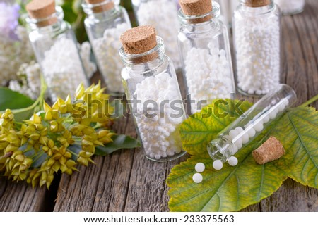 Homeopathic lactose sugar globules in glass bottles with plants - stock photo