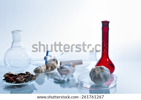 Homeopathic medicine with pills and glassware. - stock photo