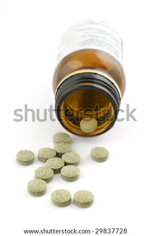 Homeopathic pills with bottle on white background - stock photo