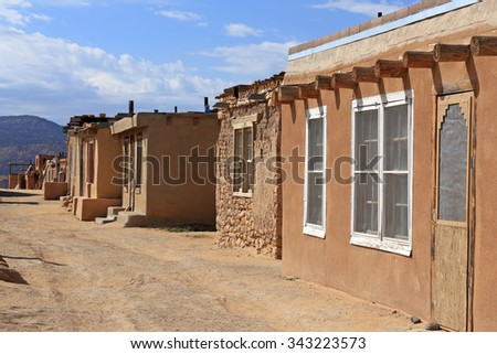 Homes in various states of repair line a dirt road at the Acoma Pueblo in New Mexico. - stock photo