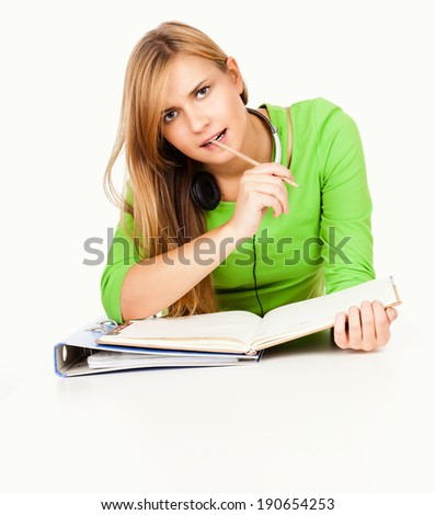 homework, young student girl writting in the folder, white background - stock photo