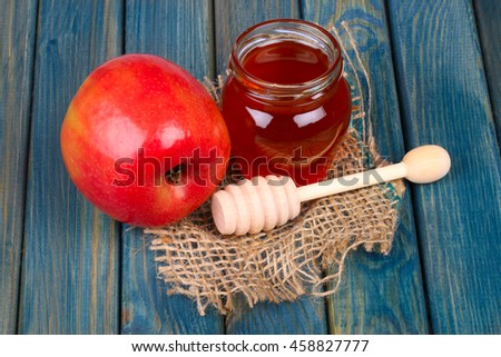Honey and apple on rustic wooden table - stock photo