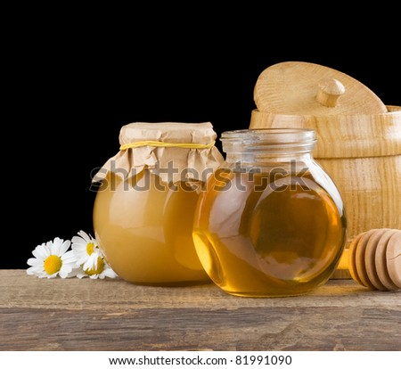 honey and flowers isolated on black background - stock photo