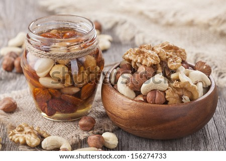 Honey and mixed nuts on wooden table - stock photo