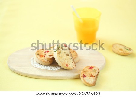 Honey and Orange Biscotti with Candied Fruits on a wooden cutting board and glass of juice on yellow background. - stock photo