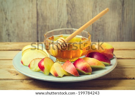 Honey and sliced apple on plate over wooden background for Jewish New Year Rosh Hashahah - stock photo