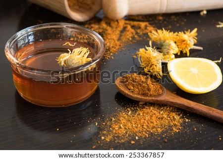 Honey and spices on dark table, dry calendula, lemon and mortar behind - stock photo