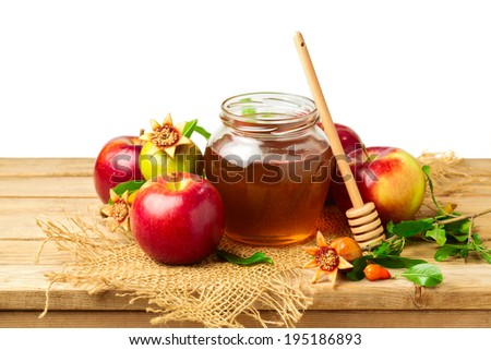 Honey, apple and pomegranate on wooden table over white background - stock photo