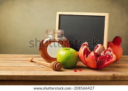 Honey, apple and pomegranate with chalkboard - stock photo