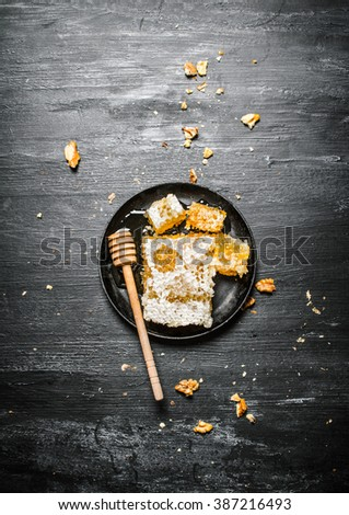 Honey background. Natural honey in honeycombs with a spoon and walnuts. On black rustic background. - stock photo