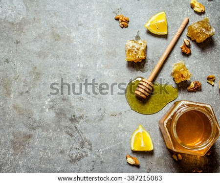 Honey background. Natural honey with slices of lemon and walnuts. On the stone table. - stock photo