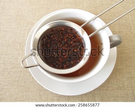 Honey bush tea in tea strainer - stock photo