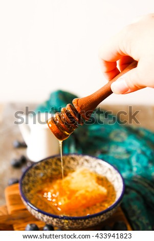 honey comb and blueberries on a stone background  - stock photo