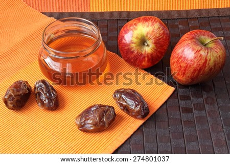 Honey, dates and apples on a bright color napkin - stock photo