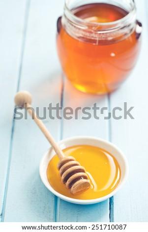 honey dipper and honey in jar - stock photo