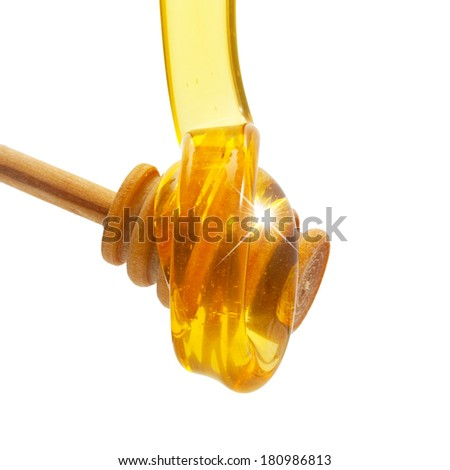 Honey drip  from wooden dipper isolated on white background - stock photo