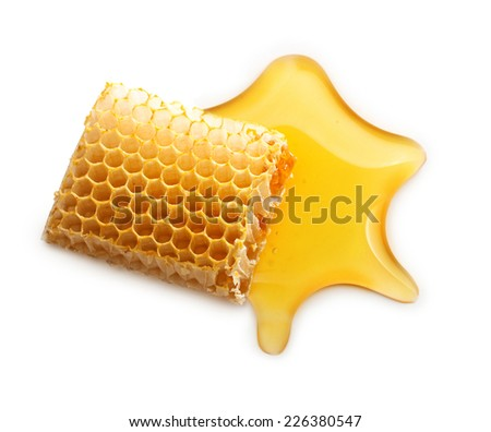 Honey drop and honeycomb on white background. - stock photo