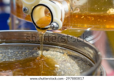 Honey extraction by honey extractor - stock photo