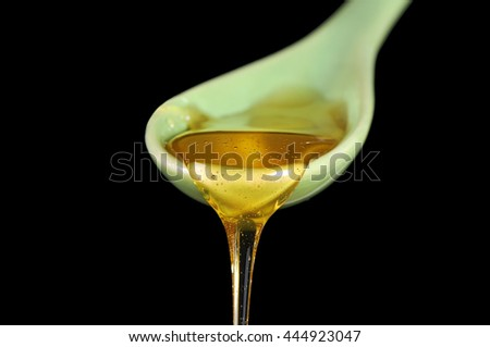 Honey flow down from a ceramic spoon. Isolated on black. - stock photo