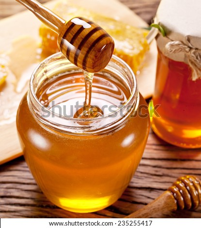 Honey flowing into glass can from wooden stick. - stock photo