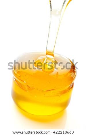 Honey flowing isolated on white background. - stock photo